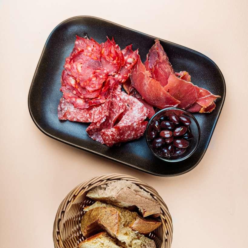 Håndskåret gris med brød og oliven